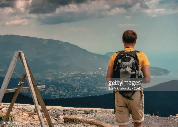 Rear View Of Man With Backpack Overlooking City On Coastline