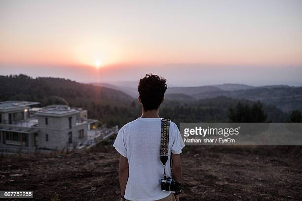 Rear View Of Man With Camera Looking At View While Standing On Mountain Against Sky
