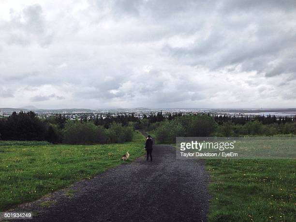 Rear view of man with dog walking on country road along landscape