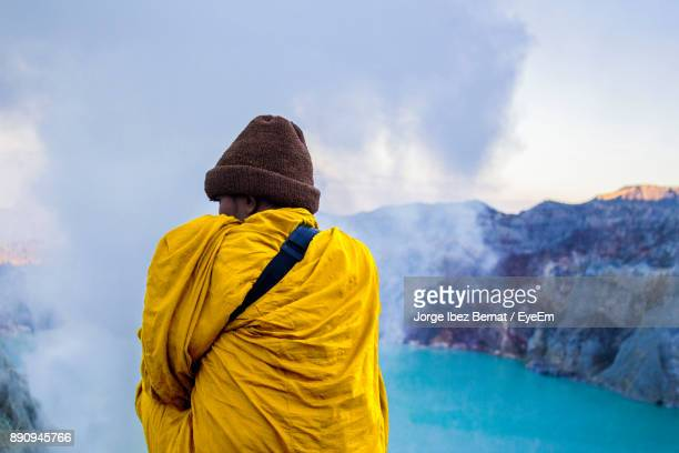 Rear View Of Man With Scarf Standing On Mountain