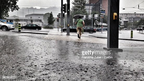 Rear View Of Man With Umbrella Running Towards Street