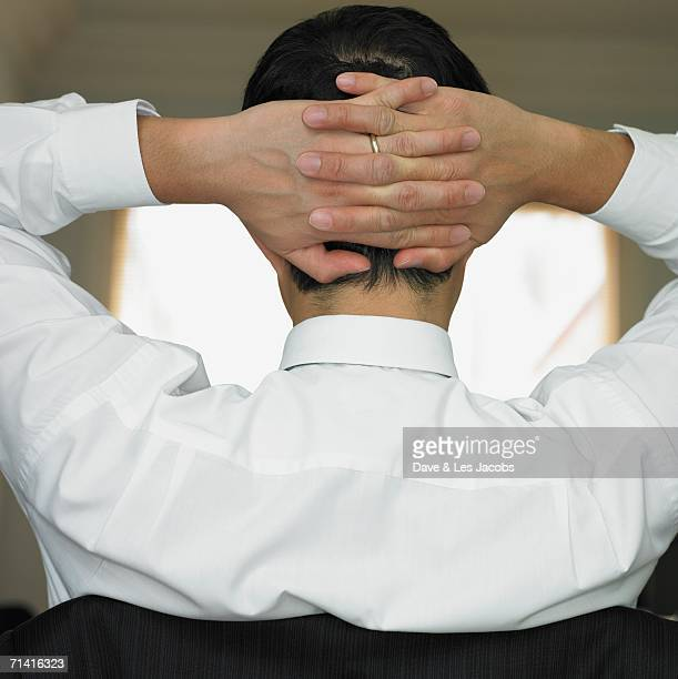 Rear view of man's hand clasped behind his head