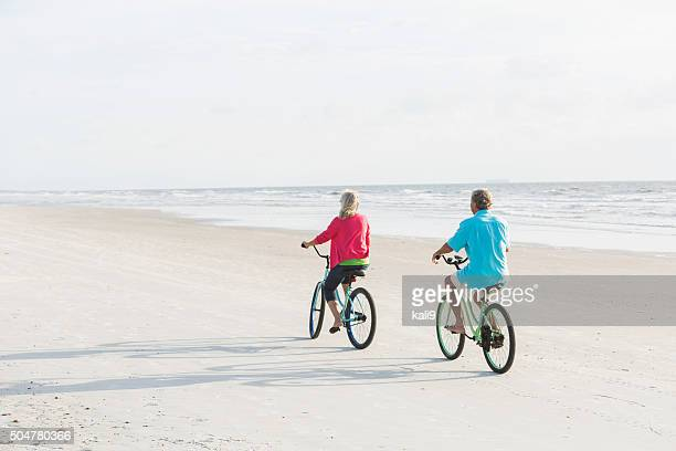 Rear view of mature couple riding bikes on the beach