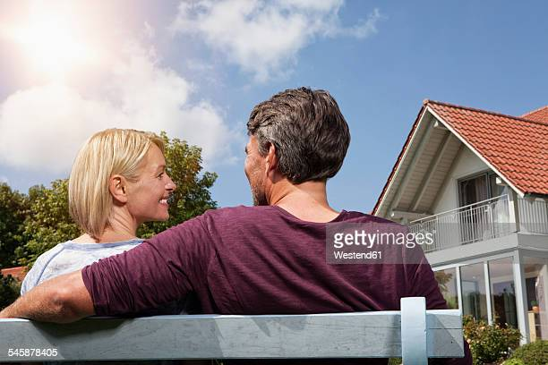 Rear view of mature couple sitting on bench in garden