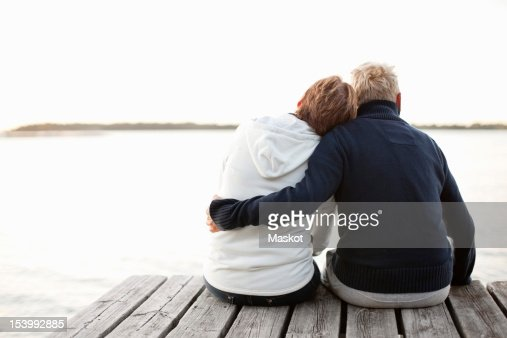Rear view of mature couple sitting on pier looking at lake