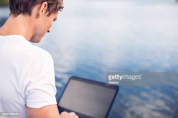 Rear view of mature man using laptop by lake