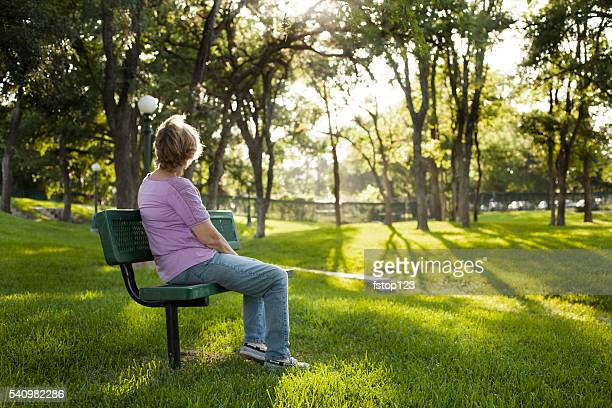 Rear view of mature woman sitting on park bench.  Summer.