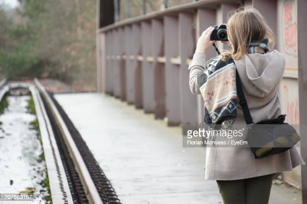Rear View Of Mature Woman Taking Selfie While Standing On Footpath