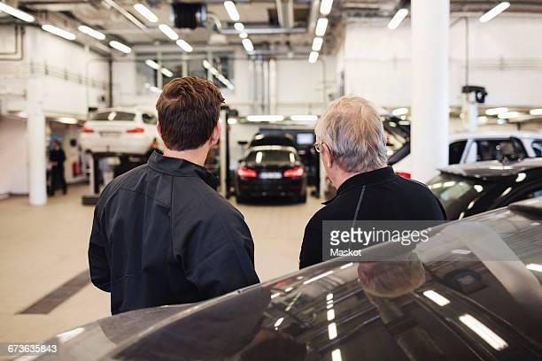 Rear view of mechanics standing in auto repair shop