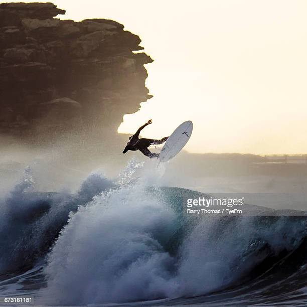 Rear View Of Men Doing Water Surfing