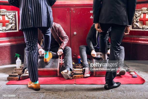 Rear view of men in suits having shoe shine, Leadenhall Market, London, England, UK