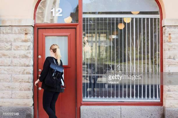 Rear view of mid adult businesswoman opening office door