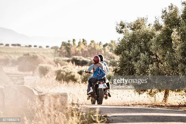 Rear view of mid adult couple riding motorcycle on dusty rural road, Cagliari, Sardinia, Italy