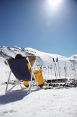 Rear view of mid adult male skier sitting on deck chair, Austria