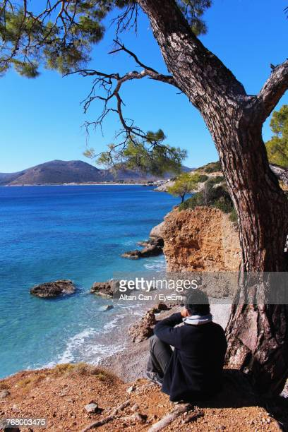Rear View Of Mid Adult Man Sitting At Beach Against Clear Sky During Sunny Day