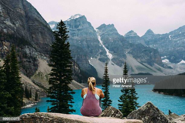 Rear view of mid adult woman on cliff edge looking at elevated view of Moraine lake, Banff National Park, Alberta Canada