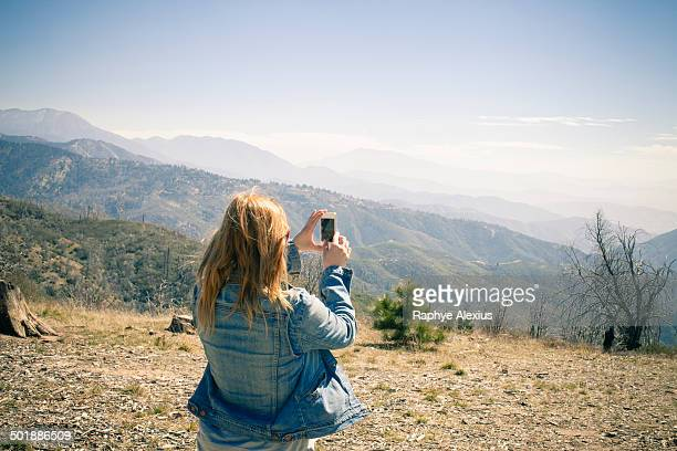 Rear view of mid adult woman photographing view on smartphone, Lake Arrowhead, California, USA