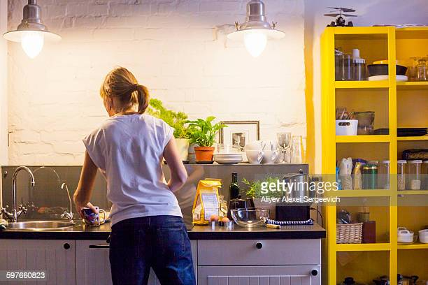 Rear view of mid adult woman preparing to bake at kitchen counter