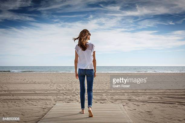 Rear view of mid adult woman strolling on beach, Castelldefels, Catalonia, Spain