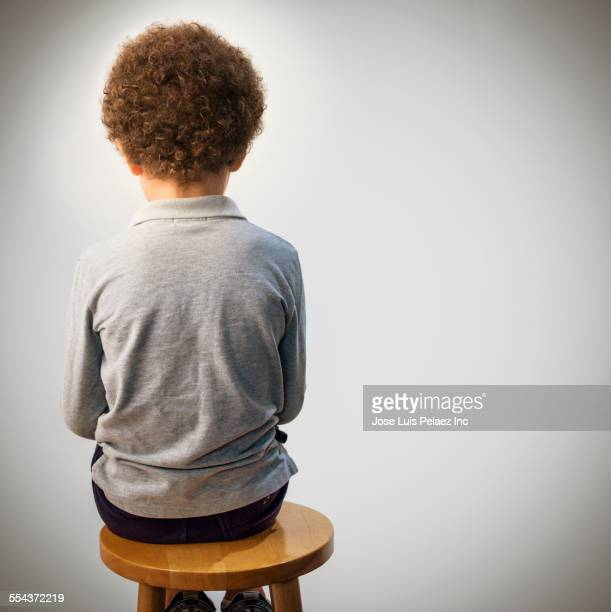 Rear view of mixed race boy sitting on stool