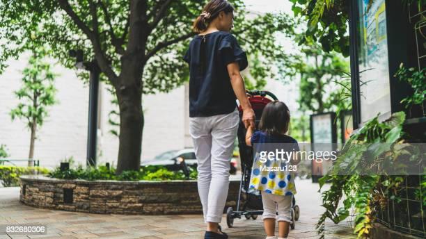Achteraanzicht van moeder en baby meisje lopen in een stadspark