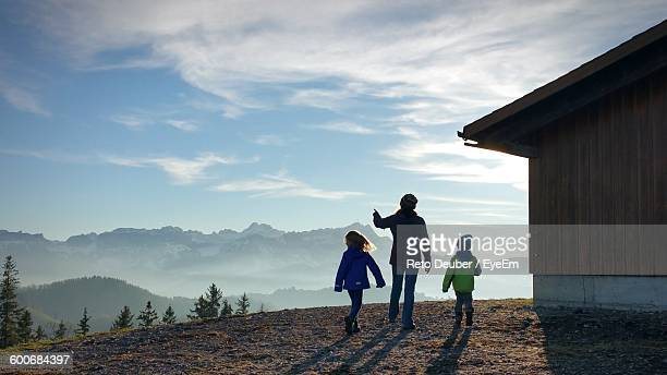 Rear View Of Mother And Children Standing On Hill Against Sky During Foggy Weather