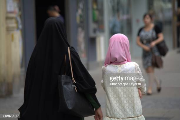 Rear View Of Mother And Daughter In Hijab Standing At City Street