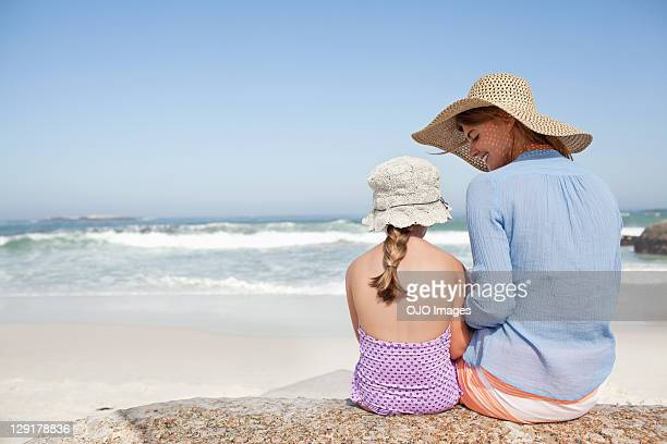 Rear view of mother and daughter sitting on rock at beach