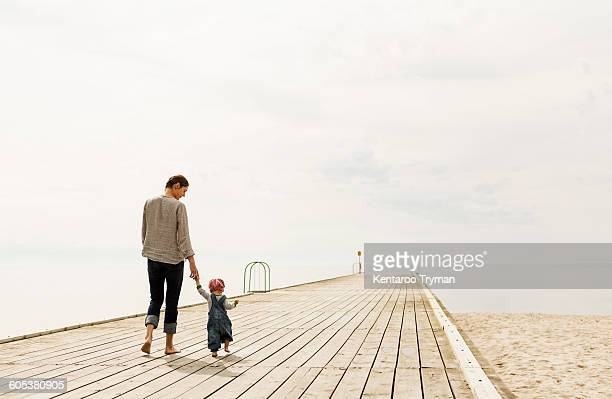Rear view of mother and daughter walking on pier at beach against sky