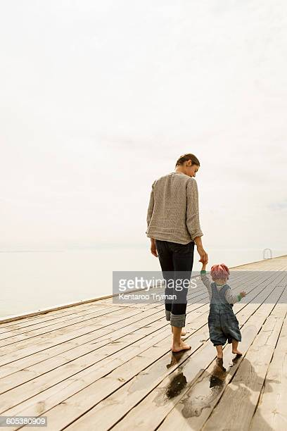 Rear view of mother and daughter walking on pier at sea against sky