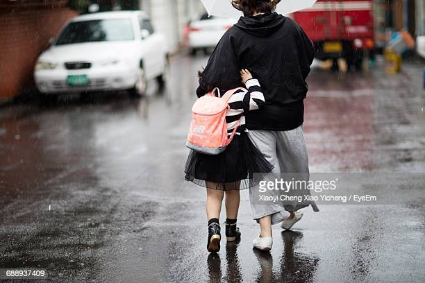 Rear View Of Mother And Daughter Walking On Wet Street