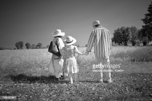 Rear View Of Mother And Father With Daughter Standing On Field During Sunny Day