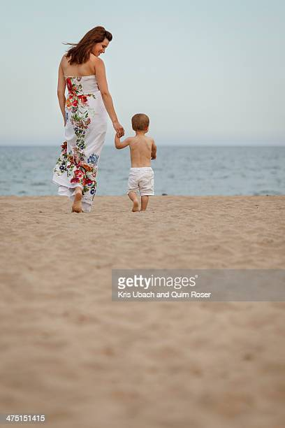 Rear view of mother and toddler walking towards sea