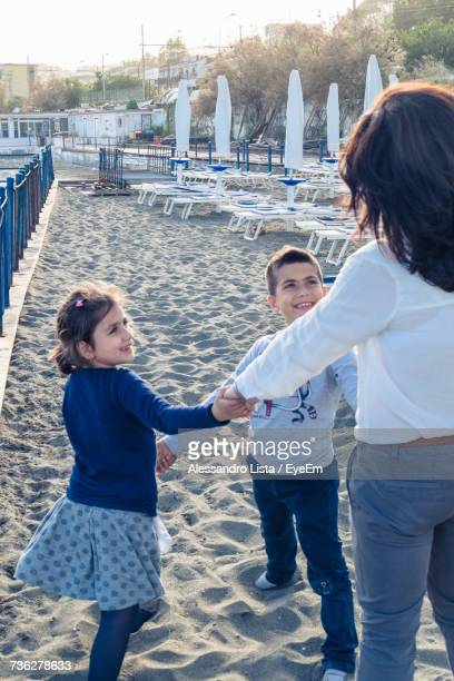 Rear View Of Mother Holding Children Hands While Standing At Beach
