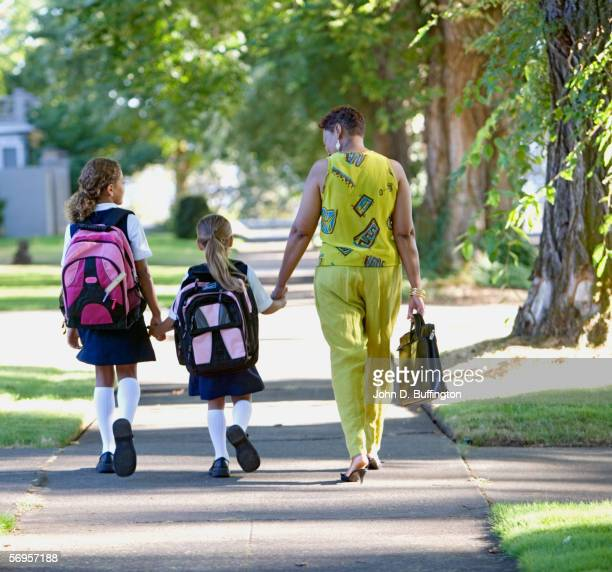 Rear view of mother with daughters walking down sidewalk