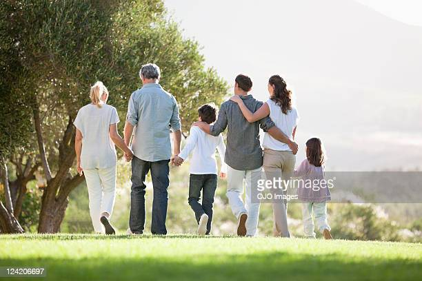 Rear view of multi generation family holding hands and walking in the park