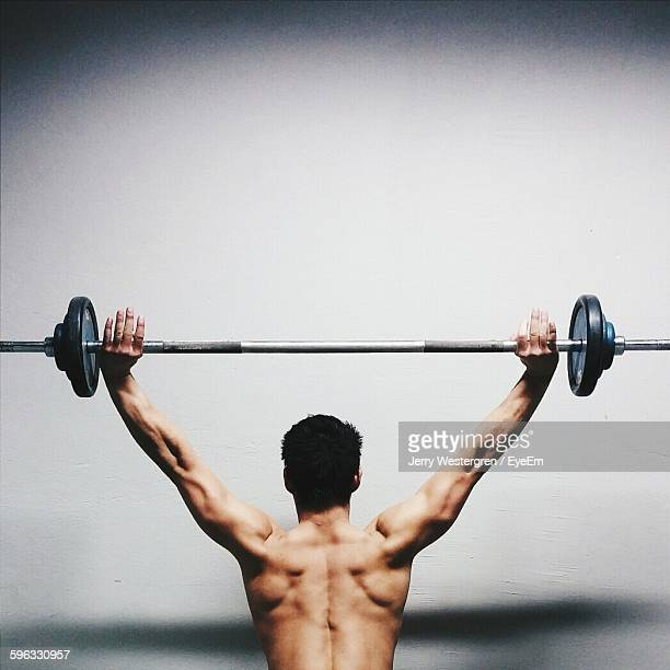 Rear View Of Muscular Man Lifted Barbell Against Wall