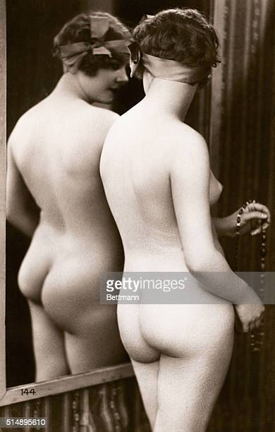 Rear View of Nude Young Woman Standing in Mirror