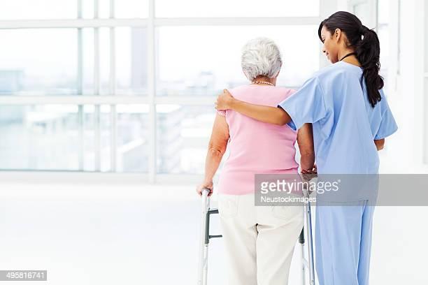 Vista posteriore di infermiera aiuta donna anziana con Deambulatore