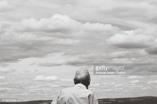 Rear View Of Old Man Against Cloudy Sky