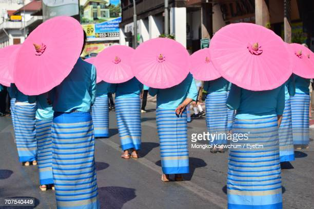 Rear View Of Parade Of Women In Traditional Clothing With Umbrella
