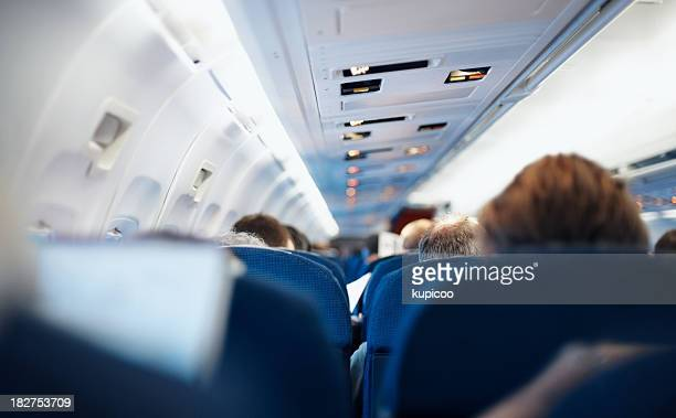 Rear view of passengers sitting in an airplane