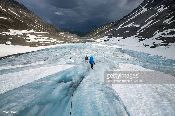 Rear View Of People Hiking On Glacier By Snowcapped Mountains Against Sky