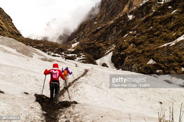 Rear View Of People Hiking On Mountain During Winter