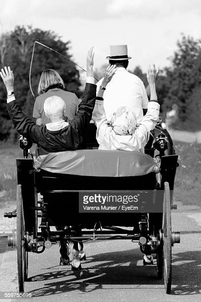 Rear View Of People In Horse Carriage
