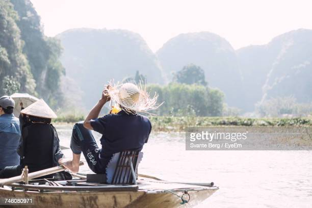 Rear View Of People On Boat Sailing In River