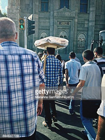 Rear View Of People Walking On Street Against Church