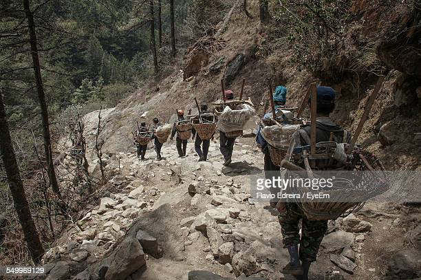 Rear View Of People With Baskets On Mountain Trail Walking Towards Namche Bazaar