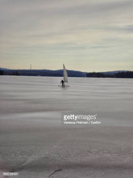 Rear View Of Person Land Yachting On Snowy Field Against Sky