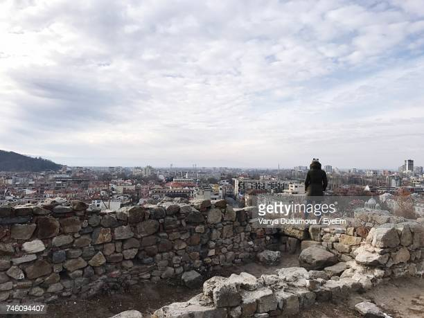 Rear View Of Person Looking At Cityscape While Standing On Old Ruin Against Cloudy Sky